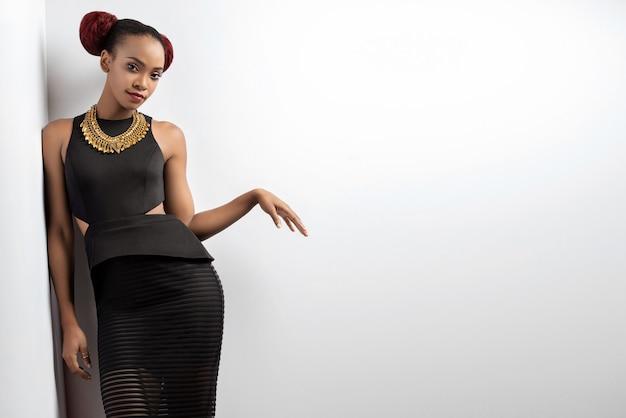 Atractiva mujer afroamericana posando cerca de la pared