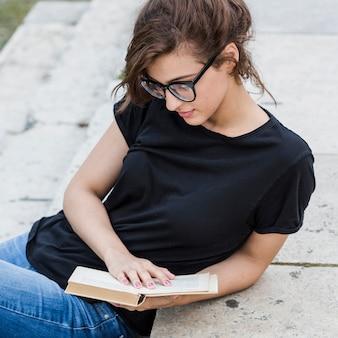 Atractiva mujer apoyándose en las escaleras con libro