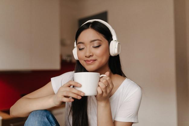 Atractiva mujer asiática en auriculares inhala aroma de té, sosteniendo la taza y sonriendo