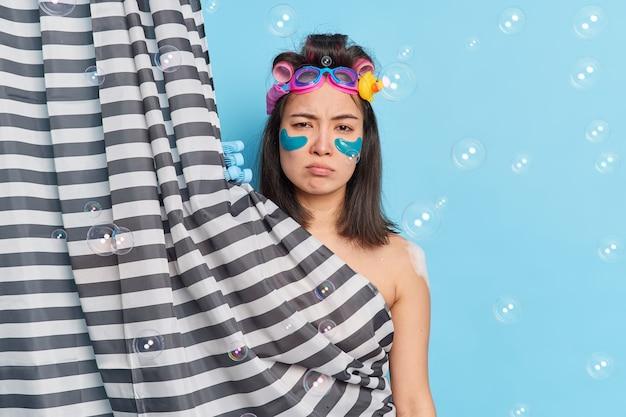 Atractiva mujer asiática disgustada toma una ducha tiene una expresión somnolienta temprano en la mañana aplica parches humectantes debajo de los ojos para reducir las líneas finas que vuelan burbujas de jabón alrededor. concepto de cuidado corporal