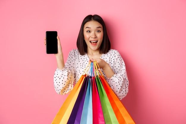 Atractiva mujer asiática que muestra la aplicación del teléfono inteligente y bolsas de compras, comprando en línea a través de la aplicación, de pie sobre rosa