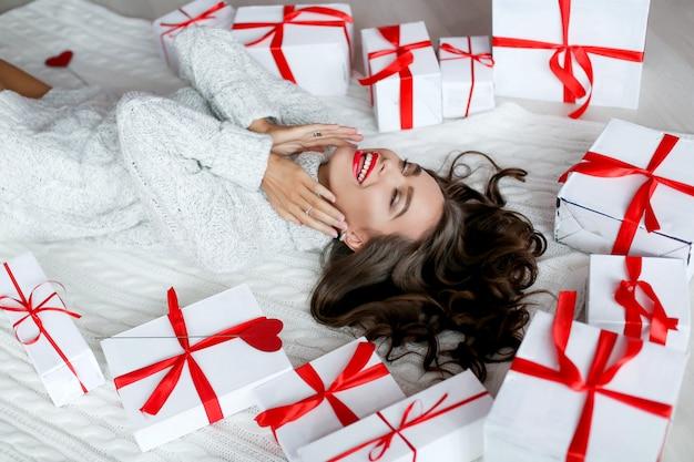 Atractiva mujer bella y sexy con sonrisa perfecta y dientes. con maquillaje en cumpleaños o día de san valentín con regalos y globos
