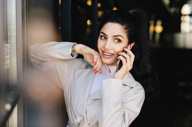 Atractiva mujer con cabello oscuro y bonitos ojos atractivos con labios carnosos vestidos con ropa elegante