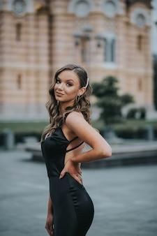 Atractiva mujer caucásica con un hermoso vestido largo negro posando en una calle