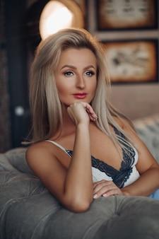 Atractiva mujer caucásica joven con cabello rubio en ropa de dormir piensa en algo