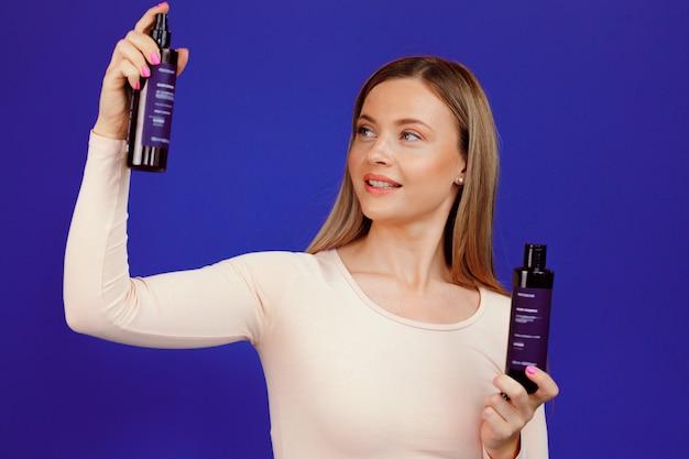 Atractiva mujer caucásica joven que presenta botellas de productos cosméticos