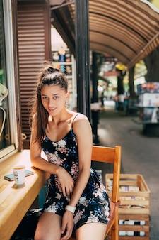 Atractiva mujer caucásica joven sentada en la cafetería de la calle