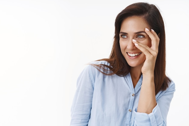 Atractiva mujer caucásica de mediana edad, tierna y femenina, se ve coqueta, se siente bien alegre, toca la cara, cuida la rutina del cuidado de la piel, gira a la izquierda en el copyspace, sonríe coqueta, pared blanca