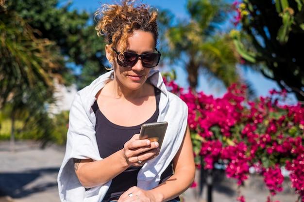 Atractiva mujer caucásica modelo de mediana edad usa el teléfono móvil para consultar el correo electrónico o para contactar y mantenerse conectado con amigos lejanos o padres concepto moderno de momento y estilo de vida cotidianos