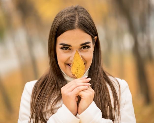 Atractiva mujer caucásica sonriendo y sosteniendo una hoja caída en el otoño Foto gratis