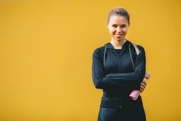 Atractiva mujer caucásica en traje deportivo con auriculares inalámbricos agua potable después del entrenamiento sobre fondo rojo-amarillo aislado