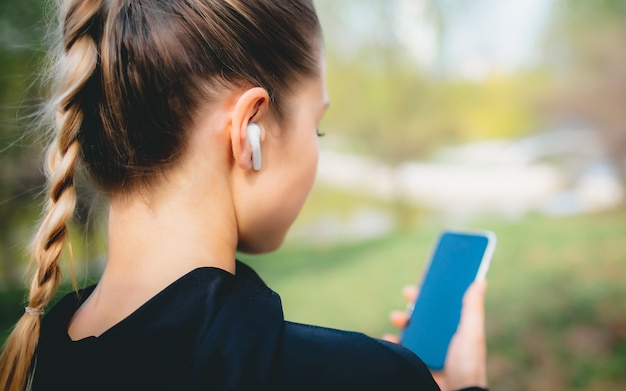 Atractiva mujer caucásica usando su teléfono, auriculares inalámbricos mientras se ejecuta en el parque