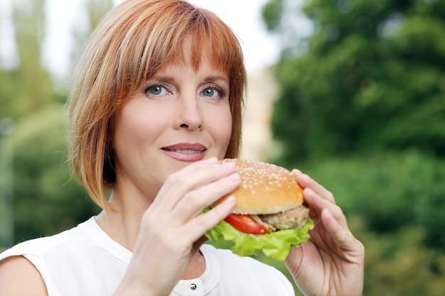 Atractiva mujer comiendo en un parque