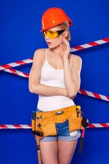 Atractiva mujer de constructor en camisa blanca, cinturón de construcción, casco, gafas de construcción, pantalones cortos de jean y risitas