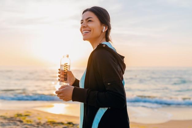 Atractiva mujer delgada haciendo ejercicios deportivos en la playa del amanecer de la mañana en ropa deportiva, agua potable sedienta en botella, estilo de vida saludable, escuchando música en auriculares inalámbricos, sonriendo feliz