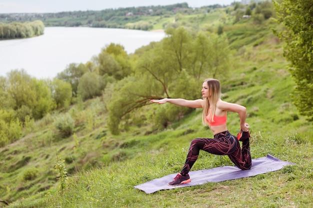 Atractiva mujer delgada está practicando yoga o pilates, gimnasia al aire libre en la orilla del río