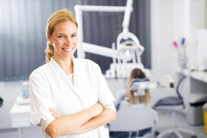 Atractiva mujer dentista posando en la moderna oficina dental