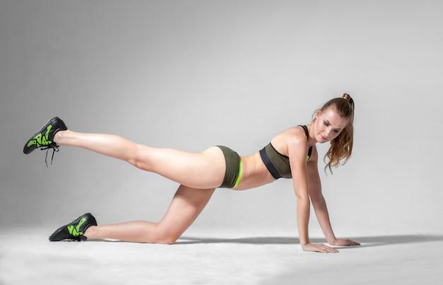 Atractiva mujer deportiva rubia caucásica haciendo ejercicio aeróbico