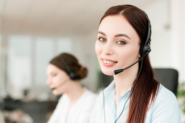 Atractiva mujer despachadora respondiendo llamadas de negocios en la oficina moderna de la compañía