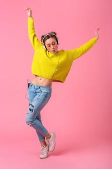 Atractiva mujer divertida feliz bailando escuchando música en auriculares vestida con traje de estilo colorido hipster aislado en pared rosa, vistiendo suéter amarillo y gafas de sol, divirtiéndose