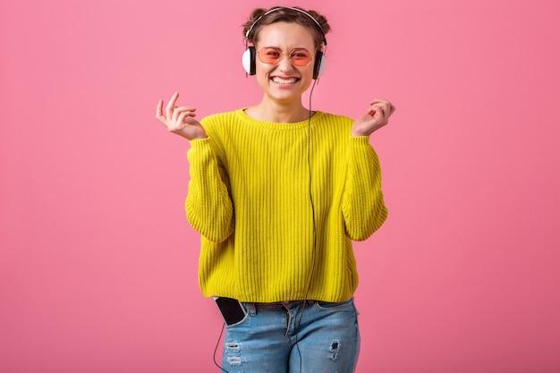Atractiva mujer divertida feliz escuchando música en auriculares vestida con traje de estilo colorido hipster aislado en pared rosa, vistiendo suéter amarillo y gafas de sol, divirtiéndose