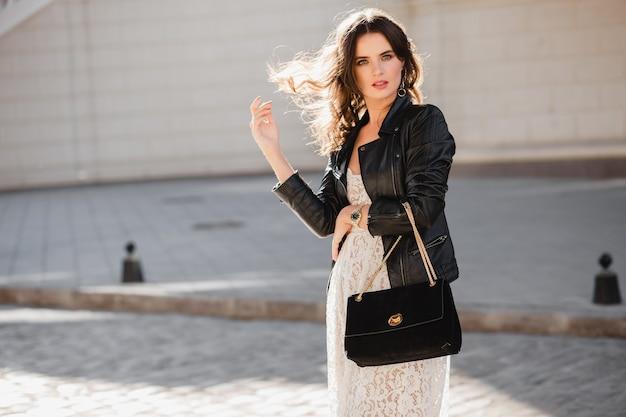 Atractiva mujer elegante caminando en la calle en traje de moda, sosteniendo el bolso de gamuza, vestida con chaqueta de cuero negro y vestido de encaje blanco, estilo primavera otoño, agitando el cabello a la luz del sol, fashionista