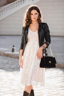 Atractiva mujer elegante caminando en la calle en traje de moda, sosteniendo el bolso, vestida con chaqueta de cuero negro y vestido de encaje blanco, estilo primavera otoño