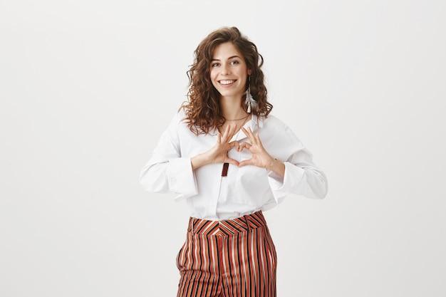 Atractiva mujer elegante mostrando el signo del corazón