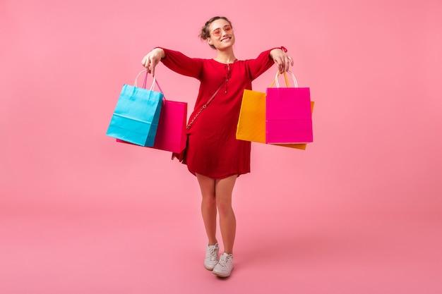 Atractiva mujer elegante sonriente feliz adicta a las compras en vestido rojo de moda con bolsas de colores en la pared rosa aislada, venta emocionada, tendencia de moda