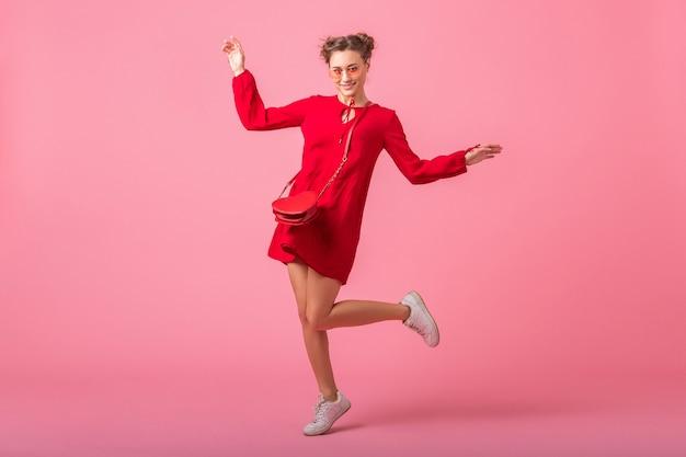 Atractiva mujer elegante sonriente feliz en vestido rojo de moda saltando corriendo en la pared rosa aislada, tendencia de moda primavera verano, chica coqueta de humor romántico
