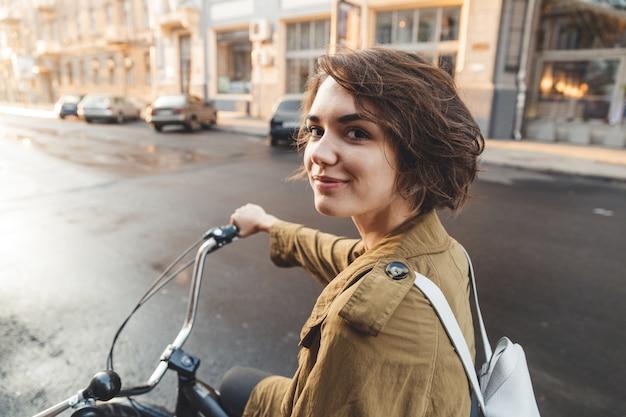 Atractiva mujer elegante vistiendo abrigo en bicicleta en una calle de la ciudad