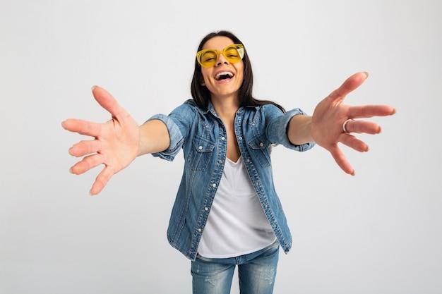 Atractiva mujer emocional riendo con los brazos abiertos a la cámara aislada en blanco