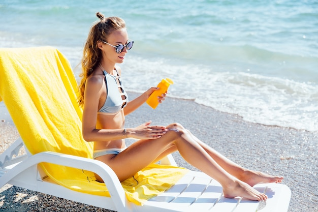 Atractiva mujer encantadora en traje de baño y gafas de sol aplicar loción solar en las piernas