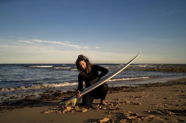 Atractiva mujer encerando su tabla de surf en la playa en españa