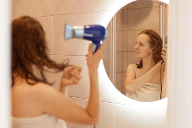 Atractiva mujer envuelta en una toalla blanca de pie con los hombros desnudos frente al espejo y secándose el cabello, haciendo procedimientos matutinos antes de ir a trabajar.