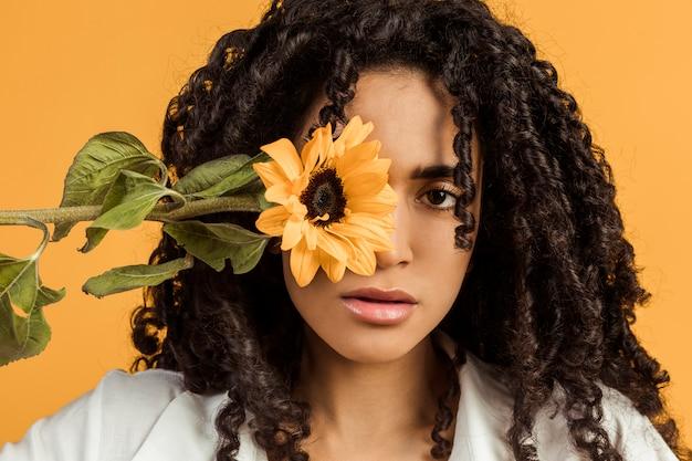 Atractiva mujer étnica con flor cubriendo ojo.