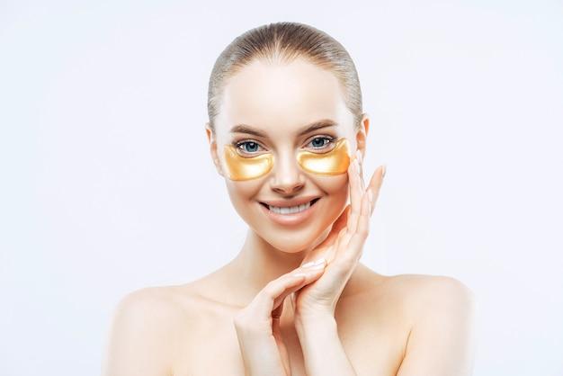 Atractiva mujer europea toca la cara suavemente, sonríe con ternura, aplica parches de hidrogel dorado debajo de los ojos