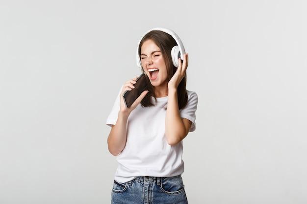 Atractiva mujer feliz jugando aplicación de karaoke, cantando en el teléfono inteligente, usando auriculares inalámbricos.