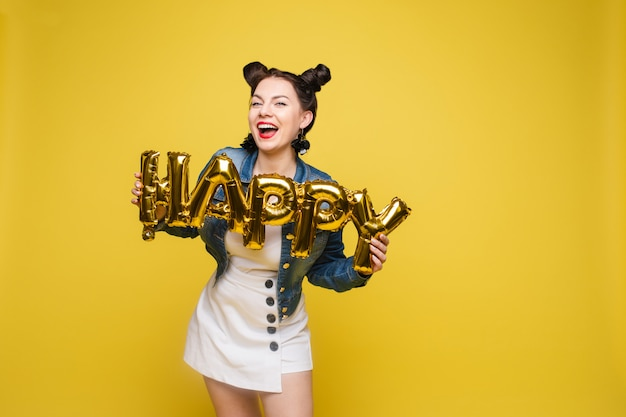 Atractiva mujer feliz riendo con grandes letras de oro posando en el fondo de estudio amarillo