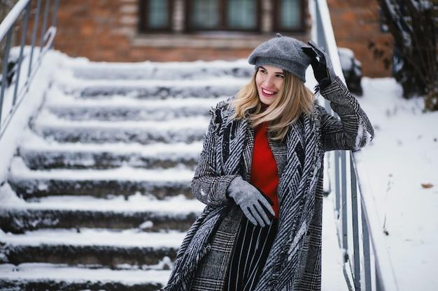 Atractiva mujer feliz en ropa de invierno cálido en una escalera nevada