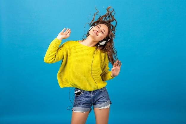 Atractiva mujer feliz sonriente bailando escuchando música en auriculares en traje elegante hipster aislado sobre fondo azul de estudio, vistiendo pantalones cortos y suéter amarillo