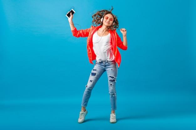 Atractiva mujer feliz sonriente bailando escuchando música en auriculares vestida con traje de estilo hipster aislado sobre fondo azul de estudio, con chaqueta rosa y gafas de sol