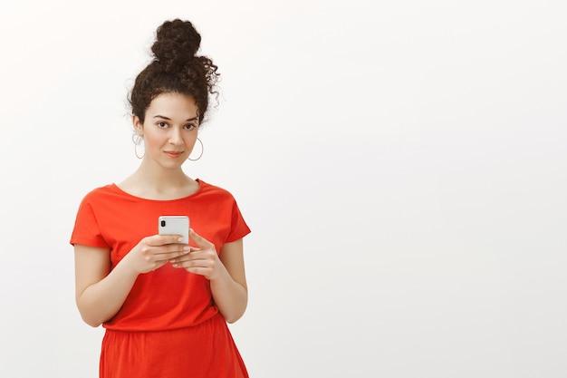Atractiva mujer femenina con estilo con el pelo rizado peinado en moño en vestido rojo