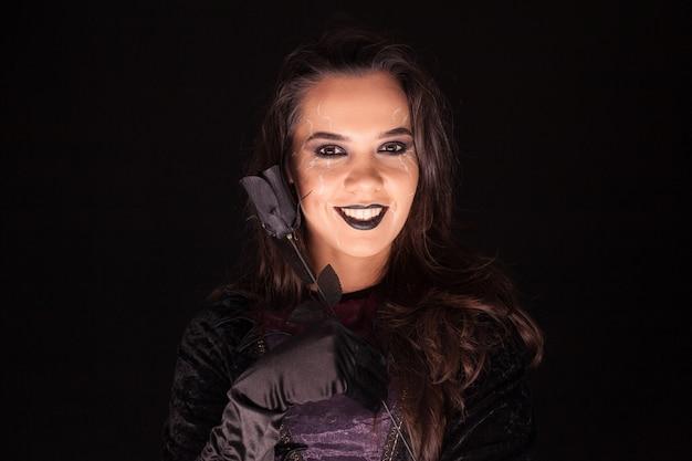 Atractiva mujer gótica vestida como una bruja para halloween.