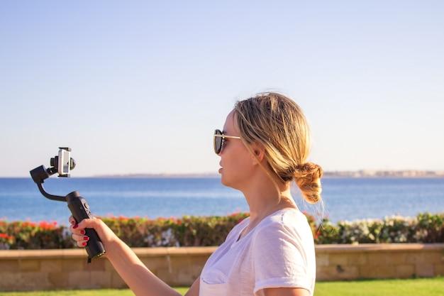 Atractiva mujer graba videos con un moderno smartphone con cámara de cardán estabilizado 3d