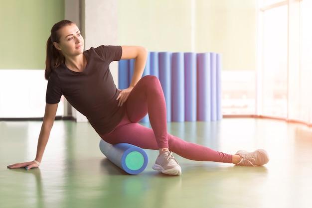 Atractiva mujer haciendo ejercicio de rodillo de espuma y posando en el moderno gimnasio brillante