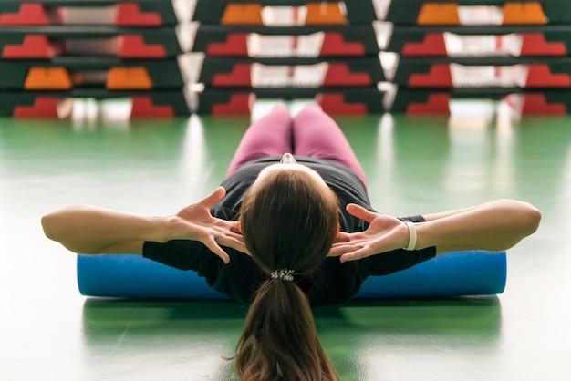 Atractiva mujer haciendo ejercicio de rodillo de espuma relajando su espalda y posando en el moderno gimnasio brillante