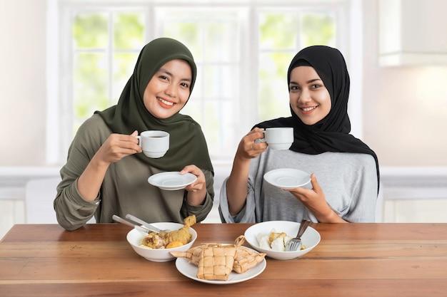 Atractiva mujer hijab desayunando comiendo un plato de pastel de arroz o ketupat