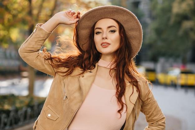 Atractiva mujer de jengibre con peinado largo posando en chaqueta beige en la pared de la calle borrosa