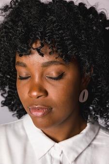 Atractiva mujer joven afroamericana con los ojos cerrados.